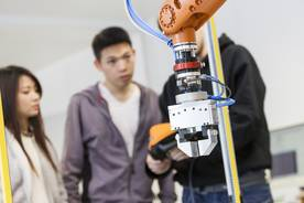 Students working with a KUKA robot